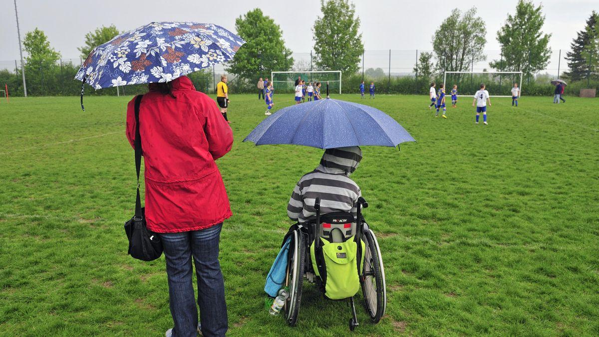 Mutter mit Sohn am Rande eines Fußballfeldes.