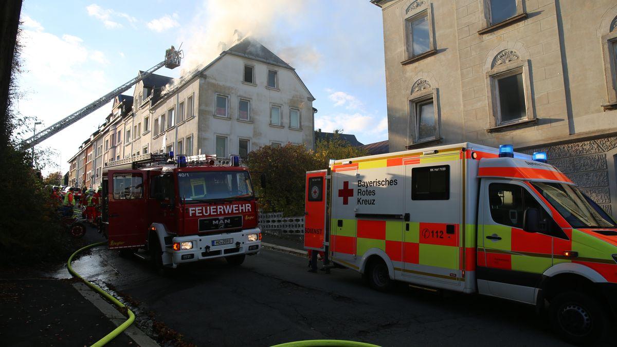 Einsatzfahrzeuge stehen vor einem Wohnhaus, aus dem Rauch aufsteigt