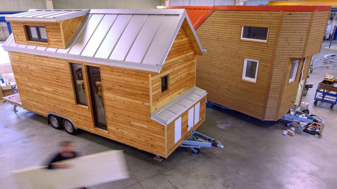 Zwei Tiny-Häuser stehen in einer Werkshalle