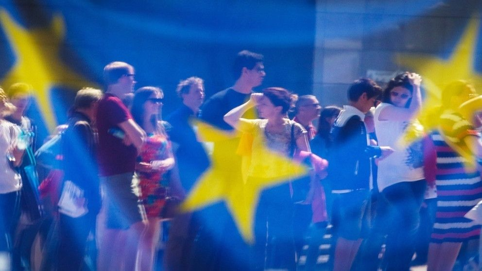 Menschen hinter transparenter EU-Flagge