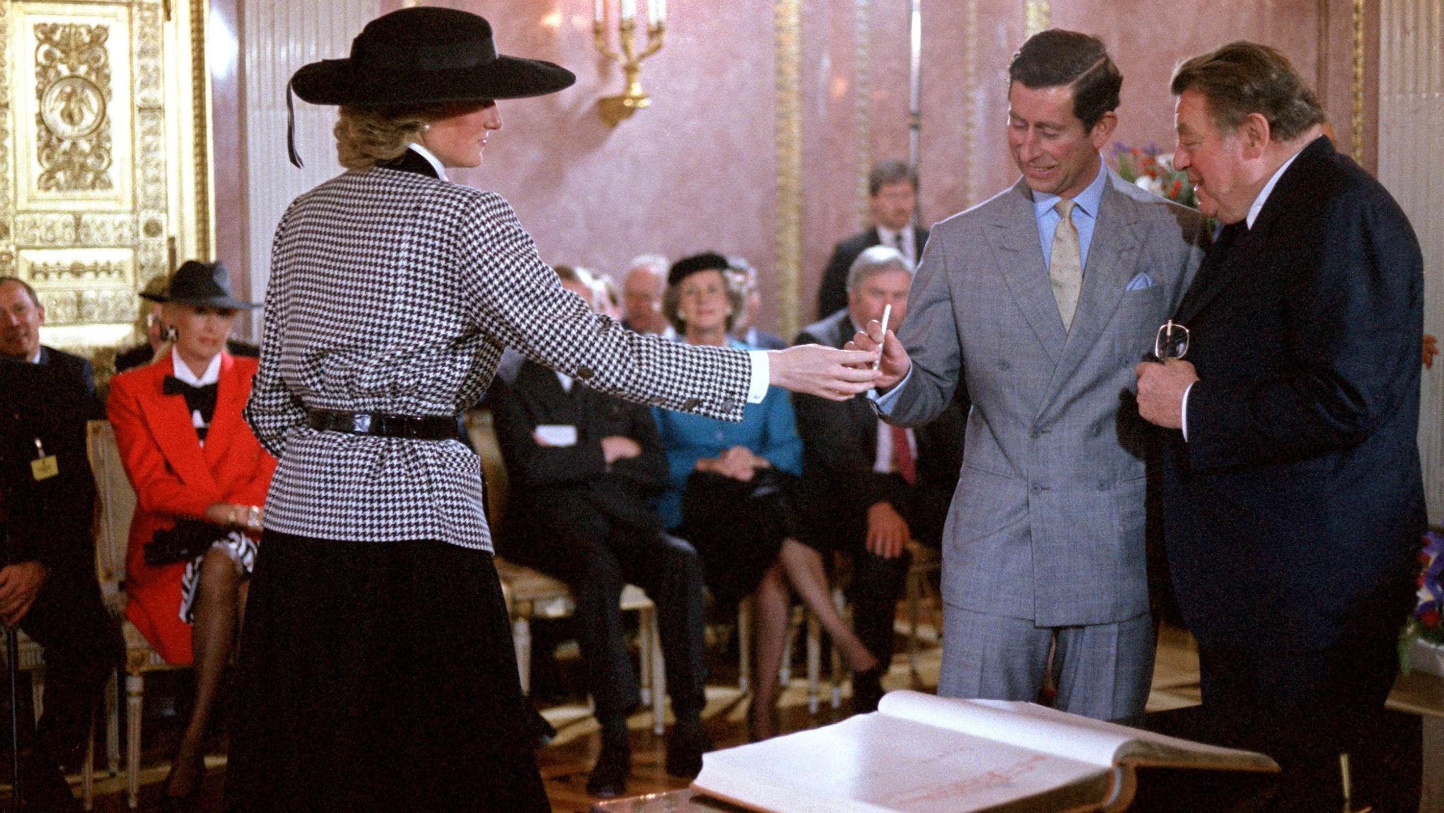 Prinzessin Diana reicht Prinz Charles einen Stift für den Eintrag in das Goldene Buch der Stadt München.