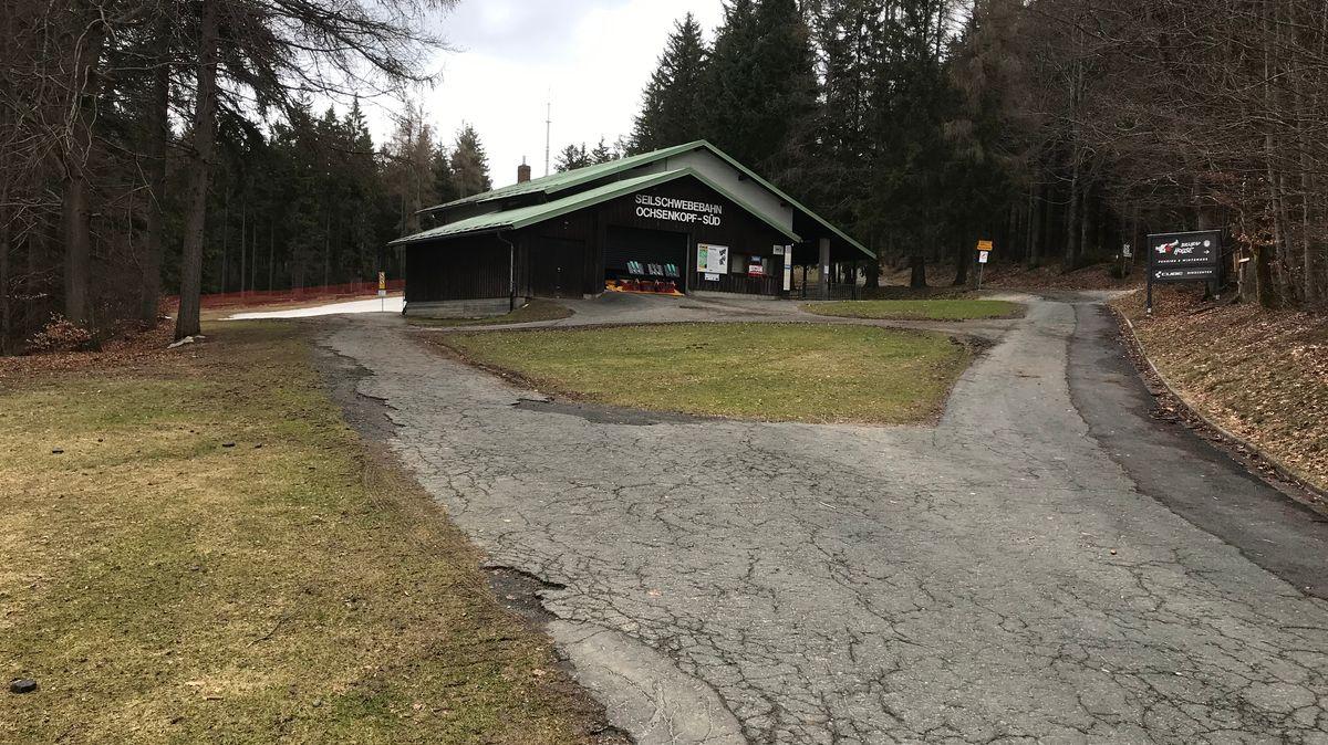 Die Talstation der Ochsenkopfseilbahn, umgeben von grünen Wiesen und grauen Straßenzufahrten.