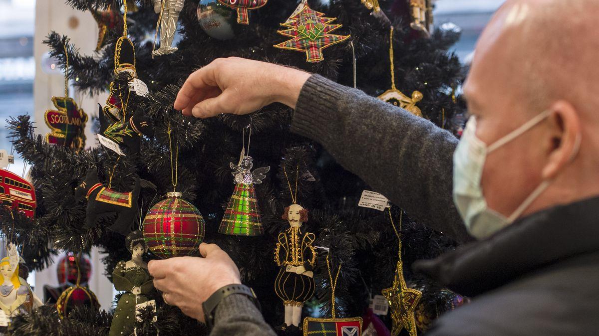 Ein Mann mit Gesichtsmaske hängt eine Kugel an einen Weihnachtsbaum.
