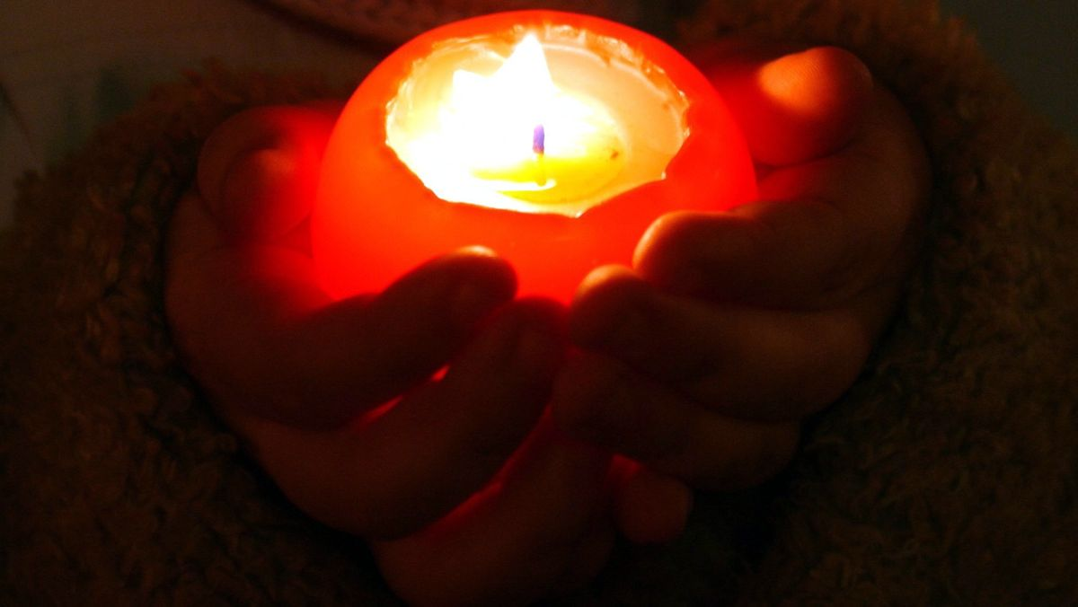 Mensch hält Kerze in den Händen