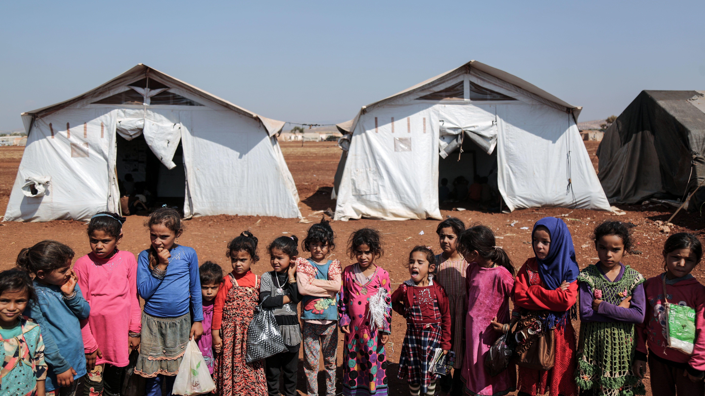 Vetriebene syrische Kinder spielen vor ihren Familienzelten in einem Flüchtlingslager nahe der syrisch-türkischen Grenze in der Provinz Idlib.