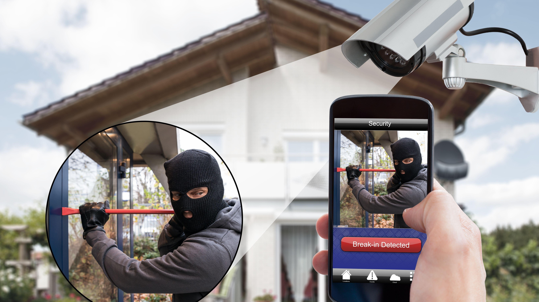 Jemand wird über sein Smartphone von einem Sicherheitssystem über einen Einbrecher in seinem Haus informiert.
