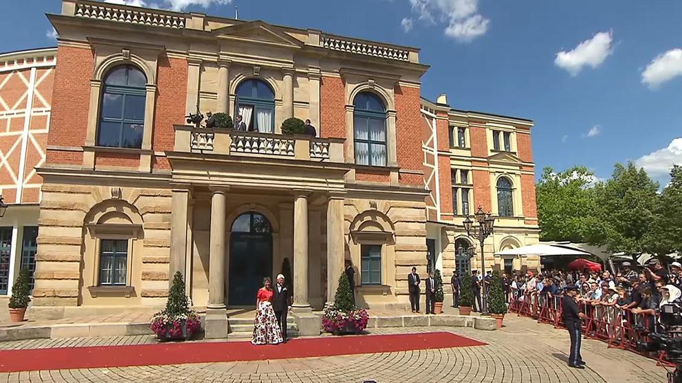 Bayreuths Oberbürgermeisterin Merk-Erbe steht mit ihrem Mann vor dem Bayreuther Festspielhaus auf dem roten Teppich.