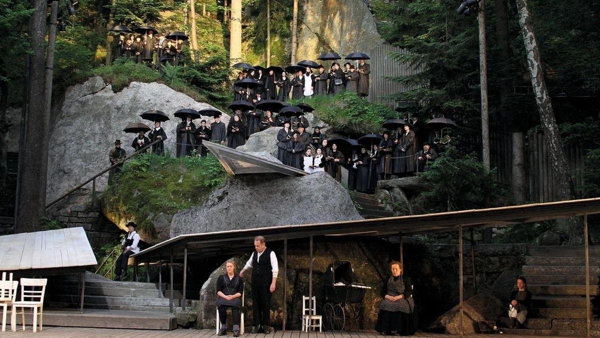 In schwarz gekleidete Schauspieler stehen mit Schirmen auf der Bühne des Freilichttheaters Wunsiedel.