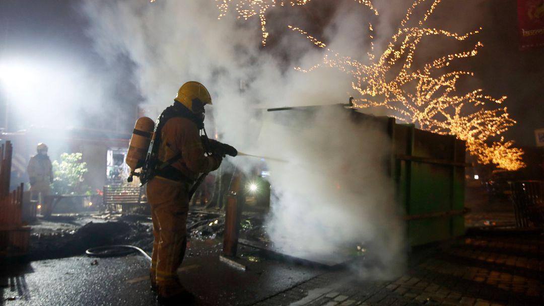 Ein Feuerwehrmann löscht einen Container, der bei Protesten gegen eine landesweite Ausgangssperre in den Niederlanden in Brand gesetzt wurde.