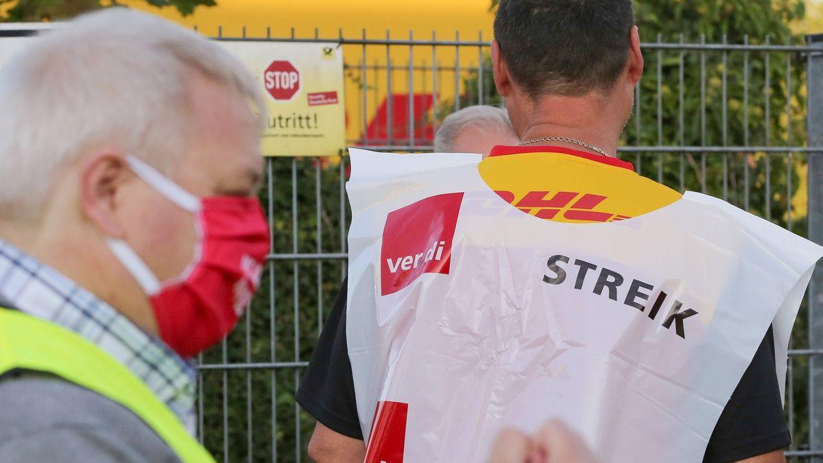 Mitarbeiter stehen bei einem Streik an einer Deutsche-Post-DHL-Niederlassung