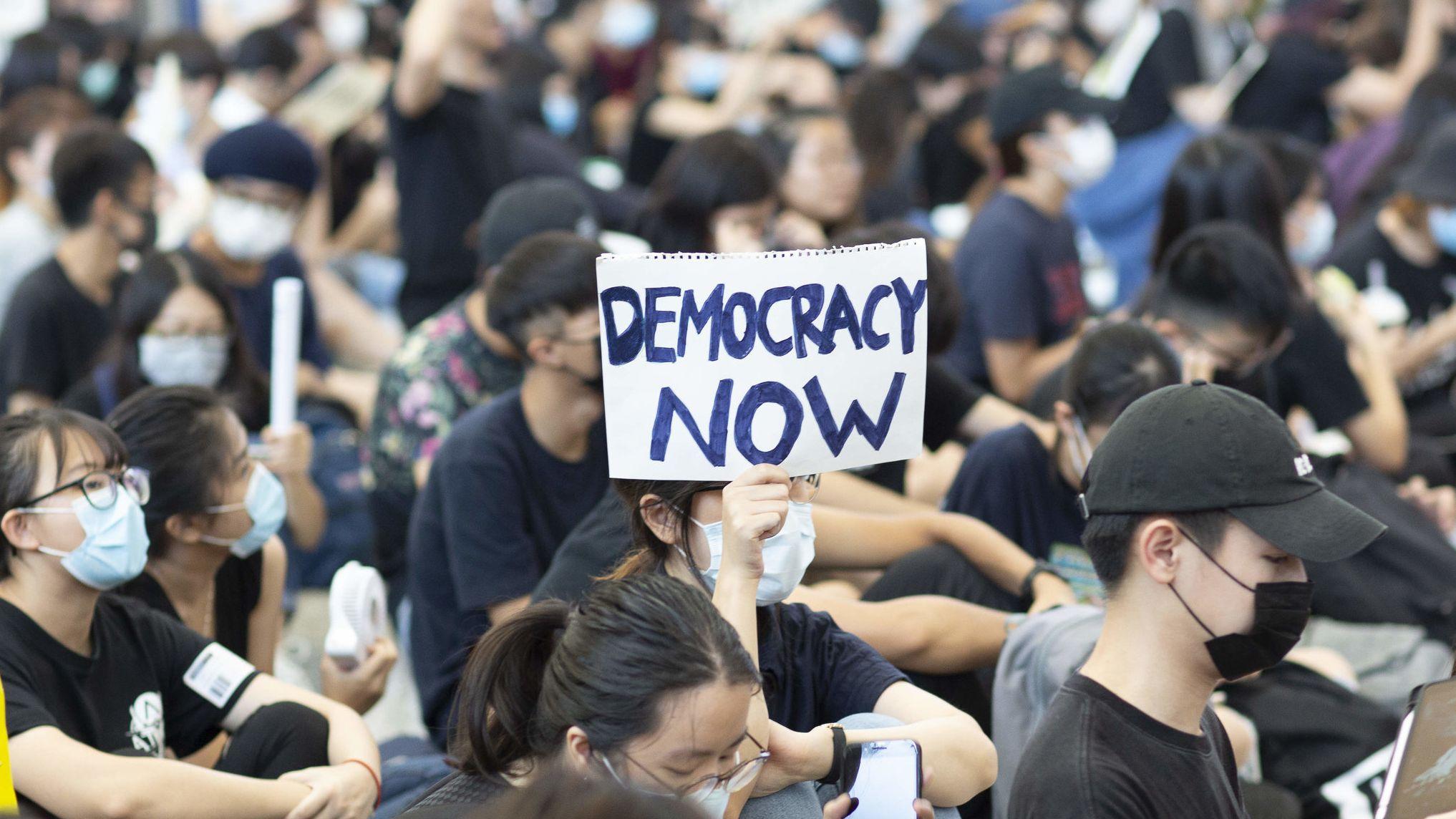 """Demonstranten in Hongkong fordern auf einem Schild """"Demokratie jetzt"""""""