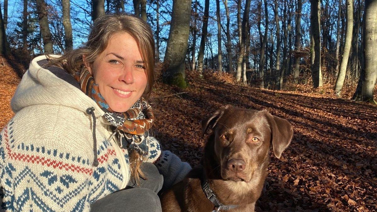 Franziska Baur mit Labrador Murmel im Wald, 2020.