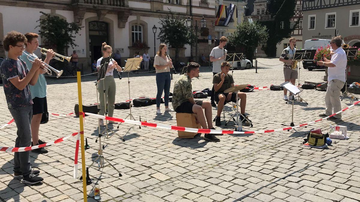 Ein Mann dirigiert eine Instrumentalgruppe mit unter anderem Trompetern und Klarinettisten, die auf einem Platz im Freien spielen.