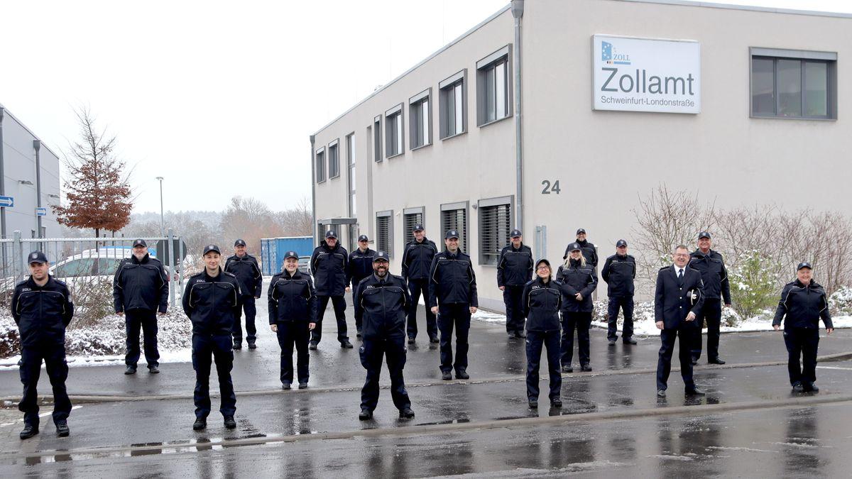 Zöllnerinnen und Zöllner stehen in ihrer neuen Dienstkleidung vor dem Zollamt Schweinfurt-Londonstraße