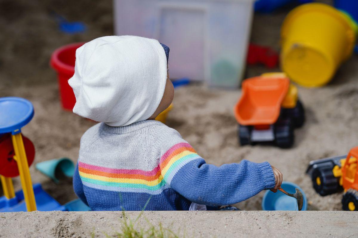 Ein Kind sitzt in einer Kindertagesstätte mit Spielzeug in einem Sandkasten.