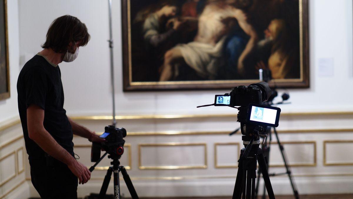 Im Hintergrund zeigt unscharf ein klassisches Ölgemälde die Beweinung Christi. Im Bildvordergrund baut jemand eine Kamera und weitere Gerätschaften auf, um das Gemälde abzulichten