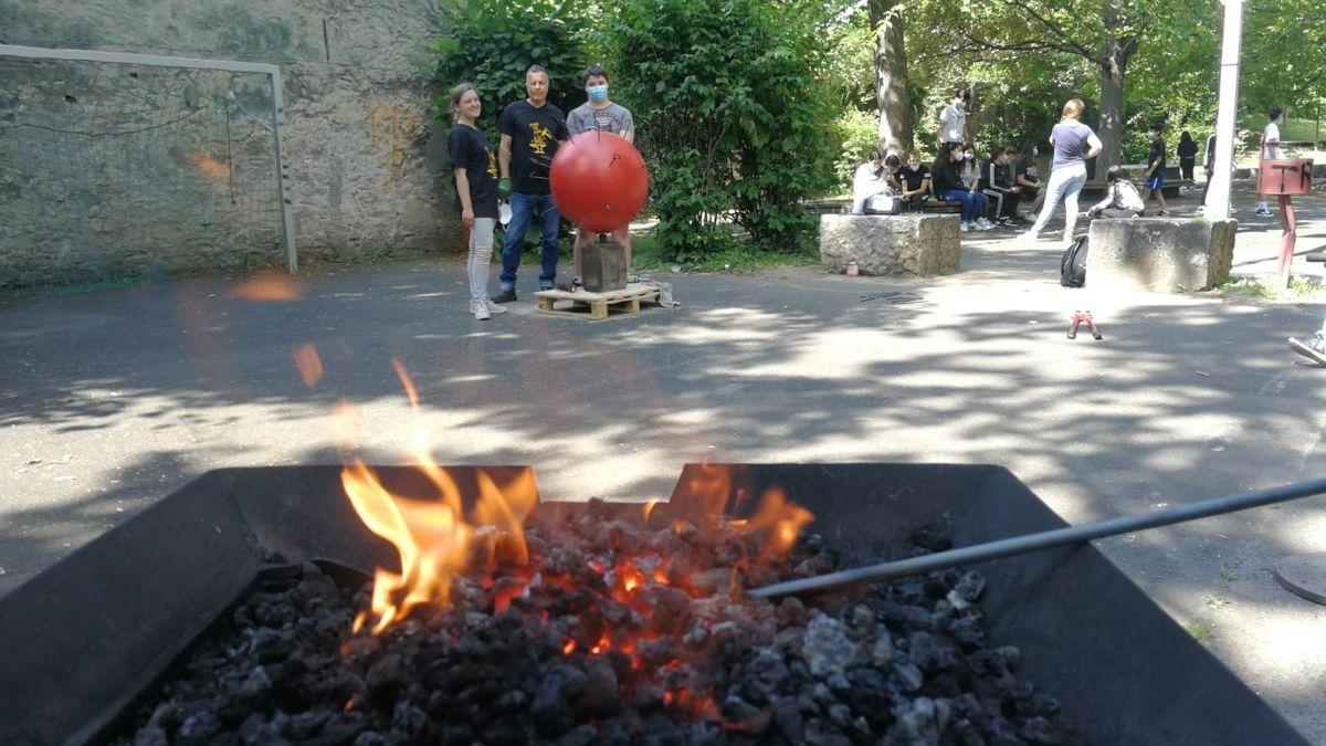 Eisenstangen werden in der Glut erhitzt, im Hintergrund die Corona-Kunst der Schüler der D.-Paul-Eber-Schule in Kitzingen