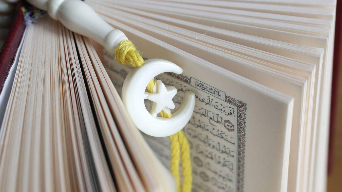 Ein Halbmond-Lesezeichen hängt zwischen Seiten des Korans.