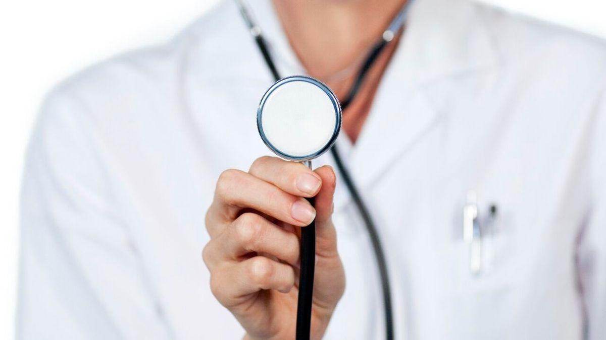 Eine Frau im Arztkittel hält ein Stethoskop