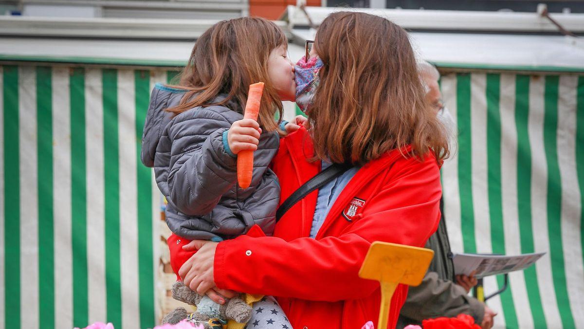 Eine Mutter mit Mund-Nasen-Schutz küsst ihre kleine Tochter.