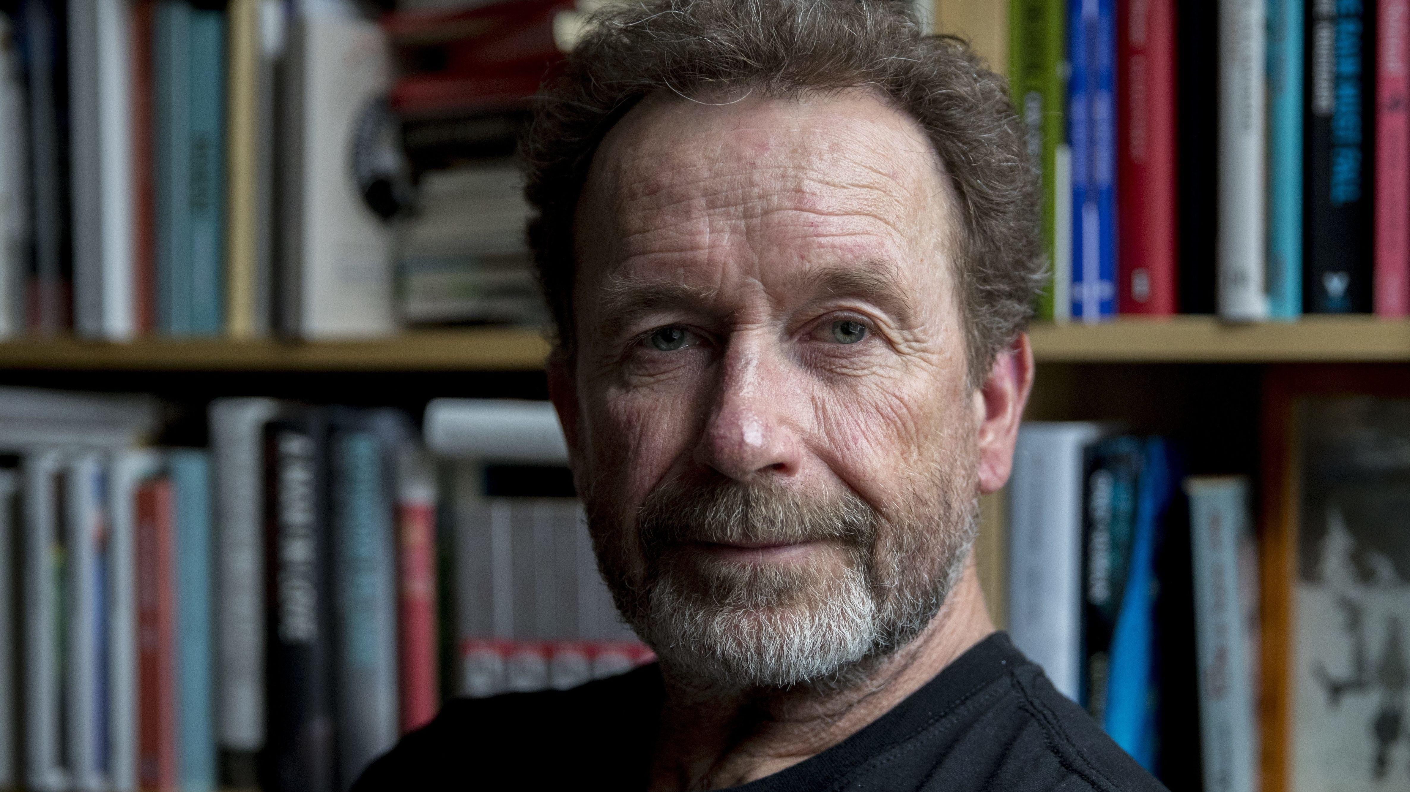 Per Petterson schaut in die Kamera. Er trägt Dreitagebart und hat leicht lichte, dunkelbraune Locken. Er steht vor einem Bücherregal.