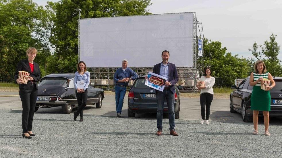 Sechs Personen (ganz links Oberbürgermeisterin Eva Döhla) stehen auf dem Volksfestplatz vor Autos und machen mit Popcorn und Plakaten Werbung für das Autokino, im Hintergrund ist eine große Leinwand aufgespannt.