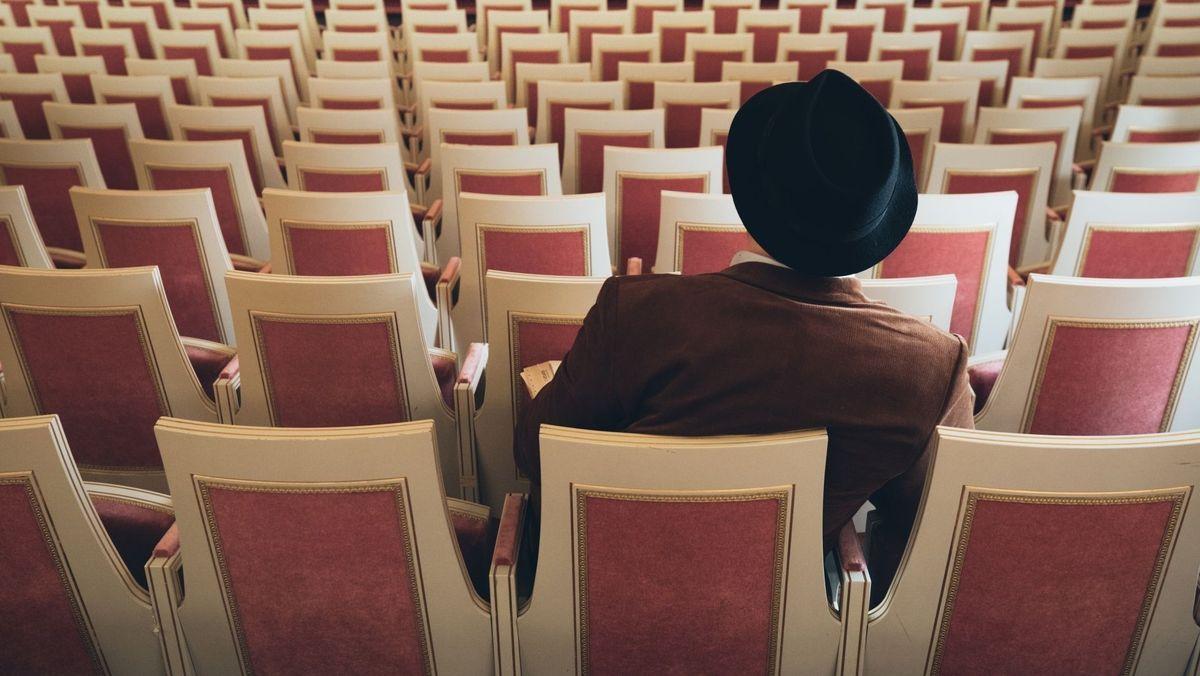 Ein Mann mit Hut in einem leeren Zuschauerraum
