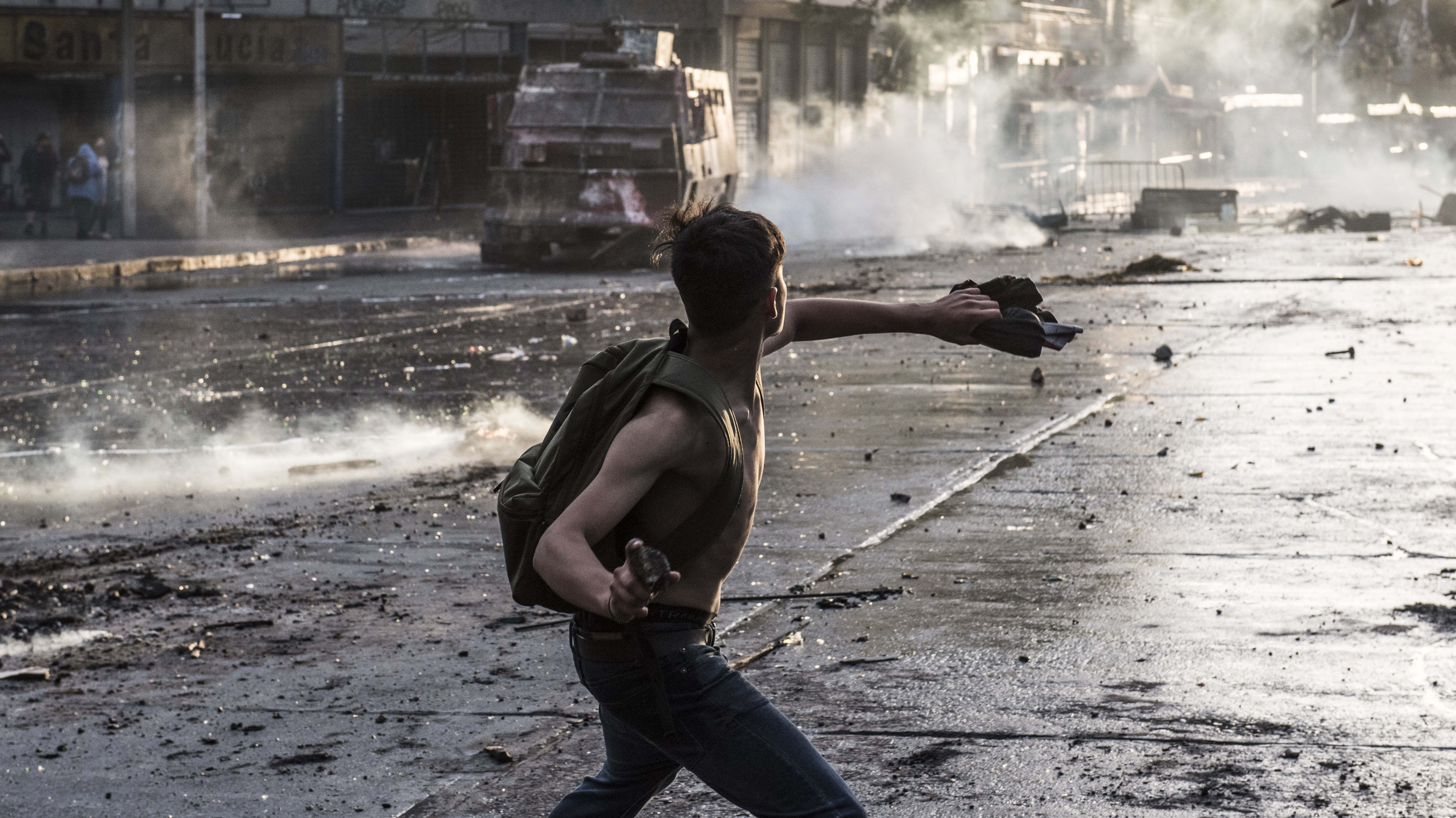 Ein junger Mann holt aus, um einen Stein zu werfen.