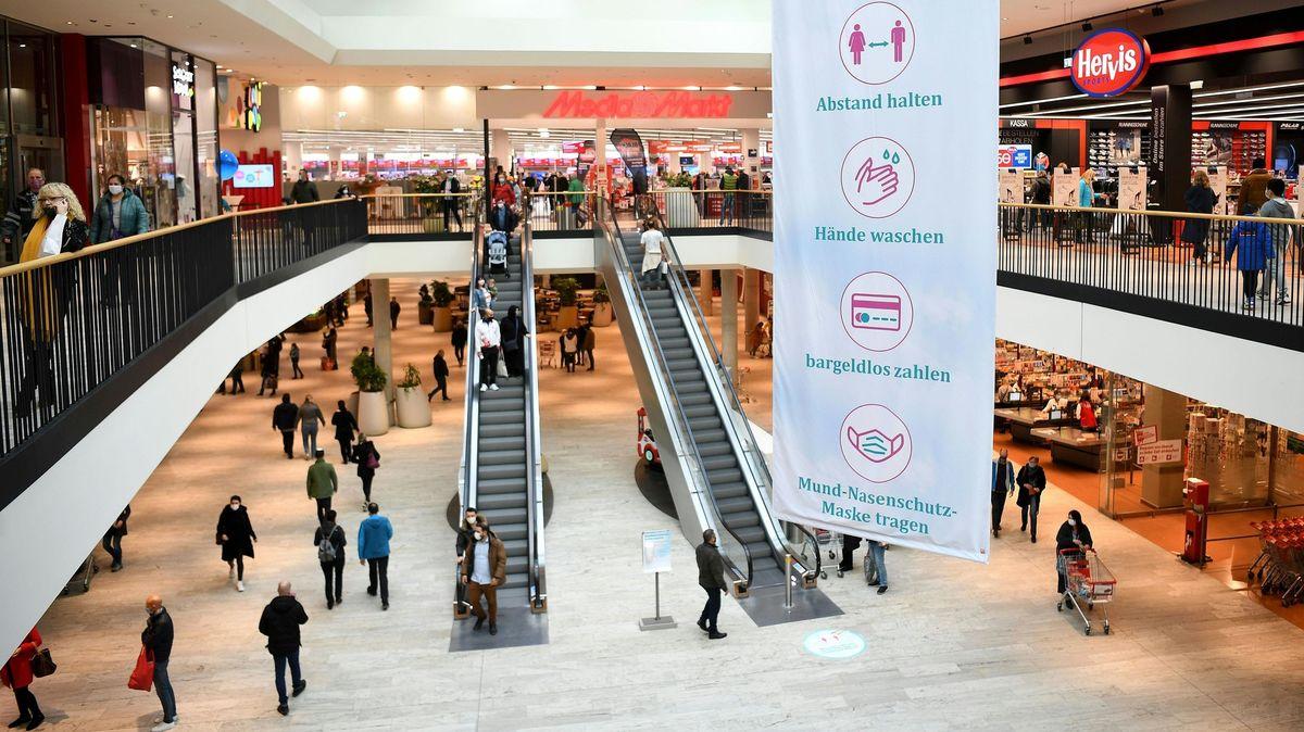 Besucher stehen in einem Einkaufszentrum