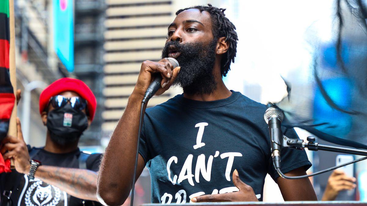 Protest gegen Rassismus und Polizeigewalt in New York: Ein schwarzer Redner spricht mit Mikrofon in der Hand, im Hintergrund steht ein Mann mit Maske und Sonnenbrille