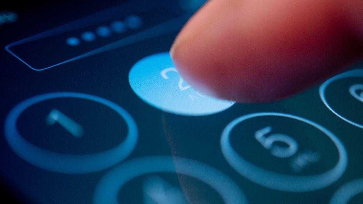 Ein Finger drückt auf einem beleuchteten Smartphone-Display auf die Ziffer zwei