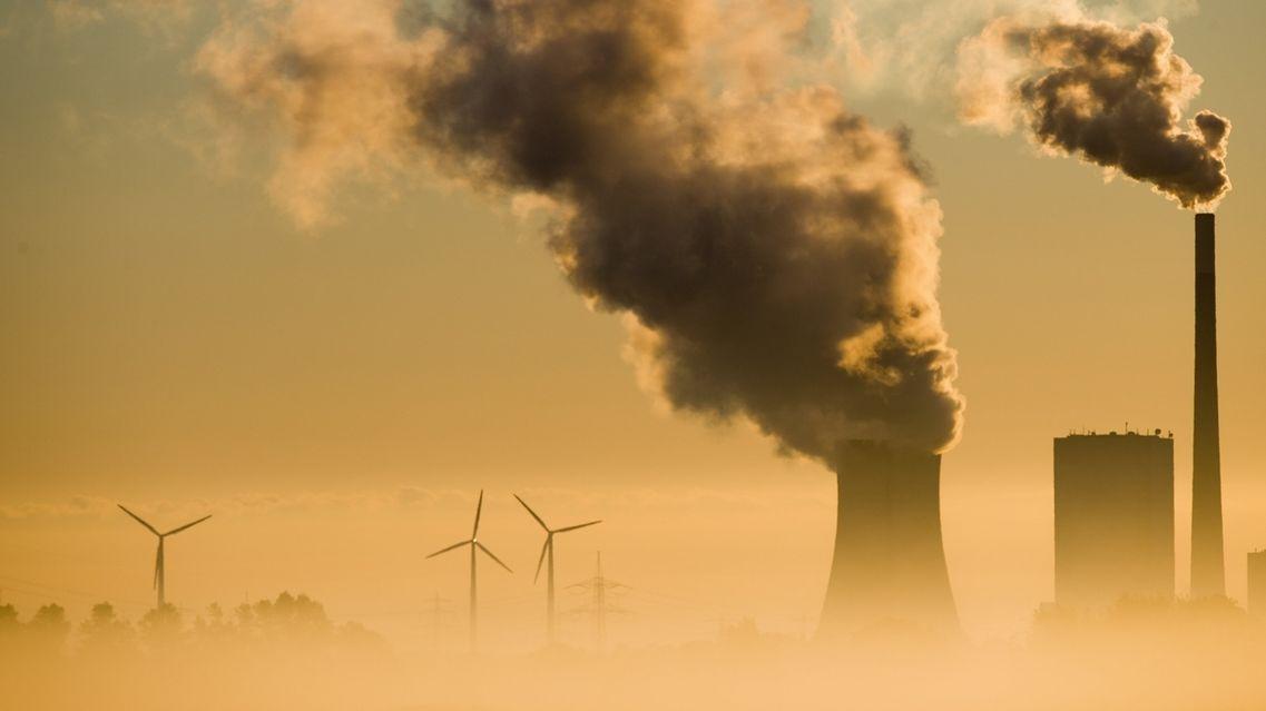 Ein Kohlekraftwerk und Windräder produzieren Strom. Mit dem Ausstieg aus der Kohle soll u.a. das Klimaschutzziel für Deutschland für 2030 erreicht werden.