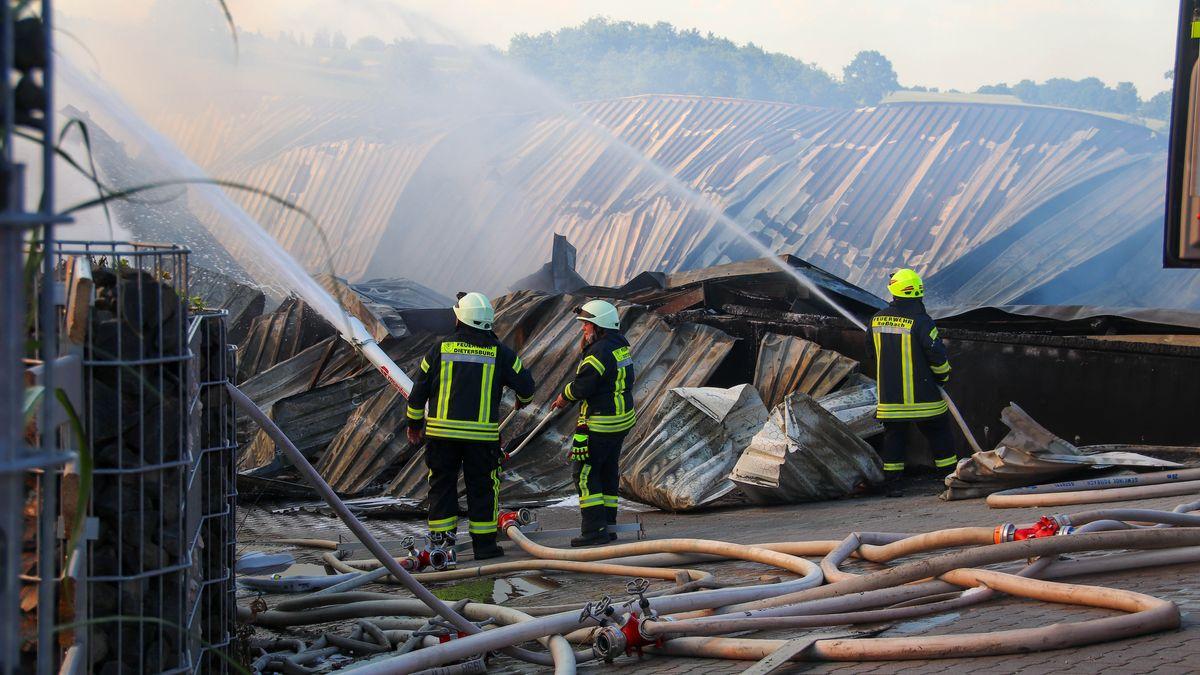 Feuerwehrleute löschen die zusammengebrochenen Hallen