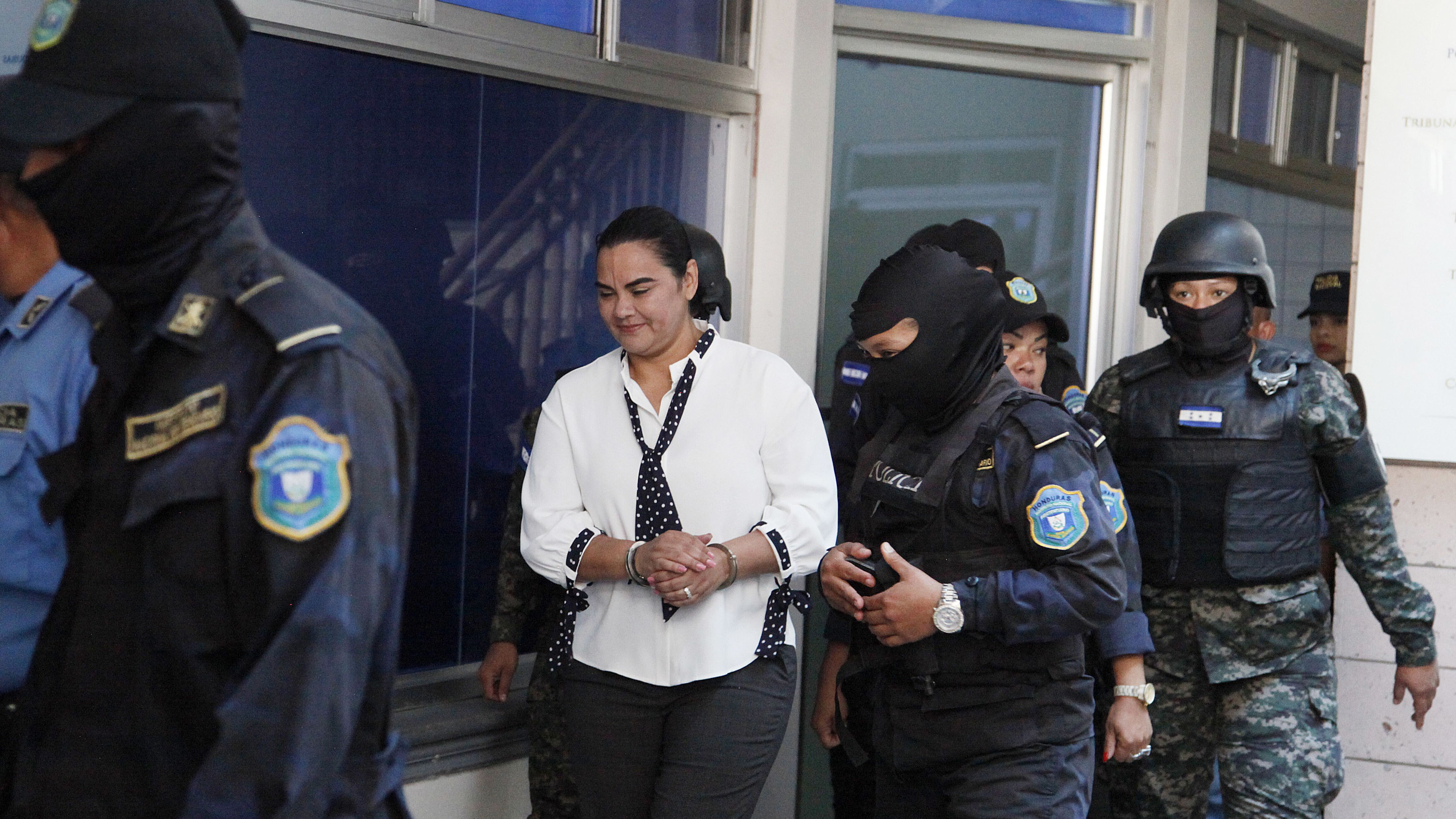 Die ehemalige First-Lady Rosa Elena Bonilla, begleitet von vermummten Polizisten, bei der Ankunft vor dem Gericht in  Tegucigalpa