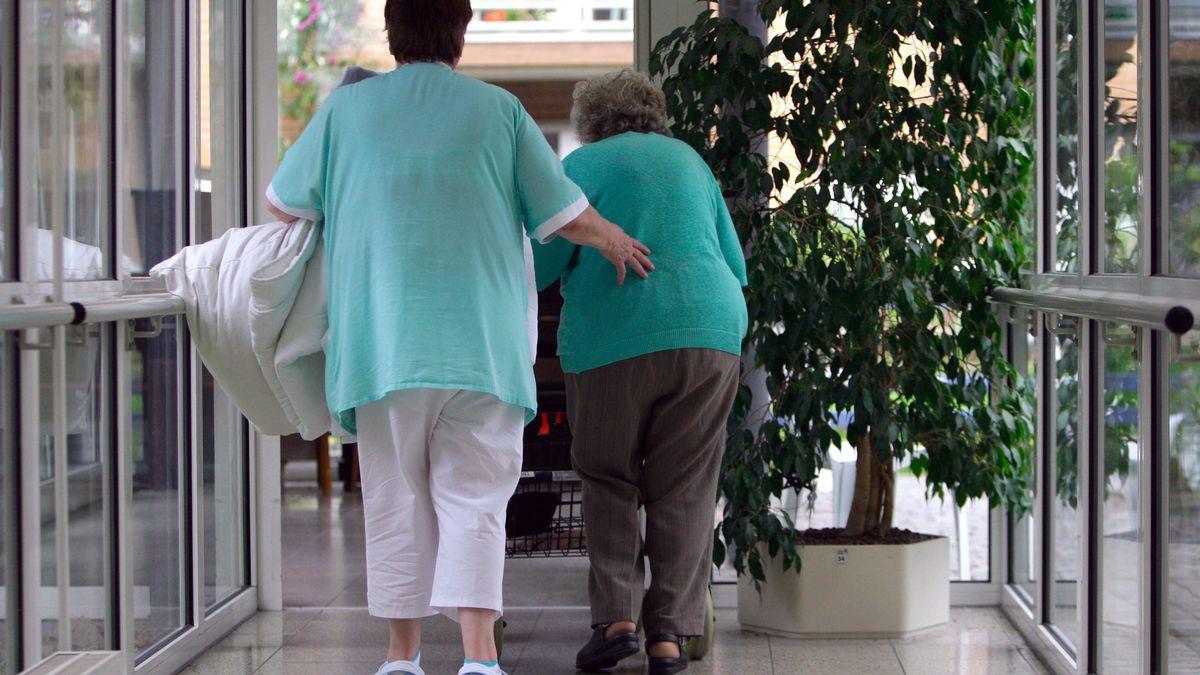 Eine Altenpflegerin geht mit einer Seniorin durch einen Flur