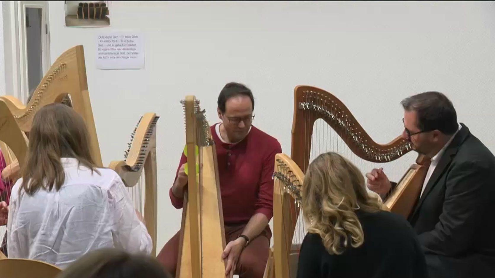 Gruppe von Harfenspielern sitzt im Kreis und spielt Johann Pachelbels Kanon in D-Dur