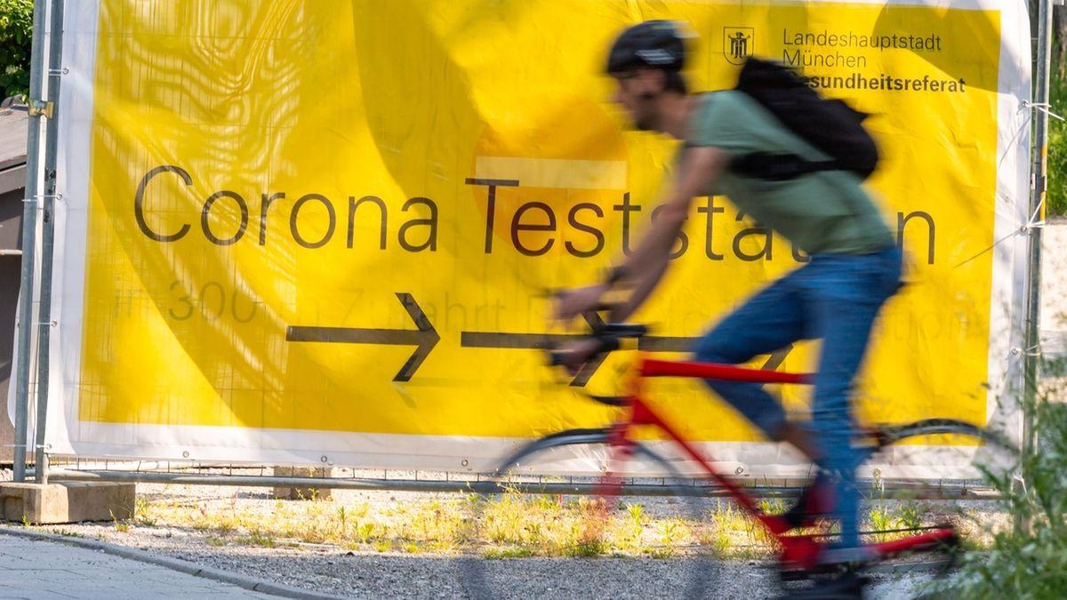 Radfahrer vor Hinweisschild Corona Teststation in München