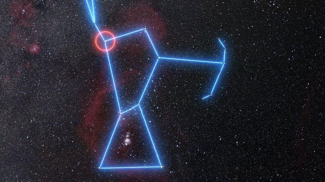 Die Weitwinkelansicht zeigt die Himmelsregion voller Sterne rund um das Sternbild Orion. Orion selbst ist mit blau leuchtenden Linien nachgezeichnet, Beteigeuze ist als Schulterstern mit einem roten Kreis markiert.