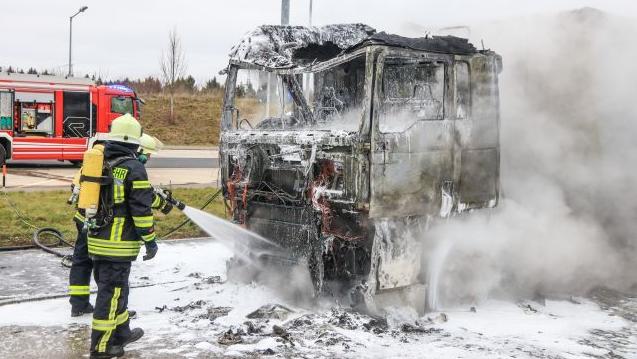 Zwei Feuerwehrmänner löschen das Führerhaus eines Lastwagens, das komplett ausbrannte, im Hintergrund ist ein rotes Feuerwehrauto zu sehen.
