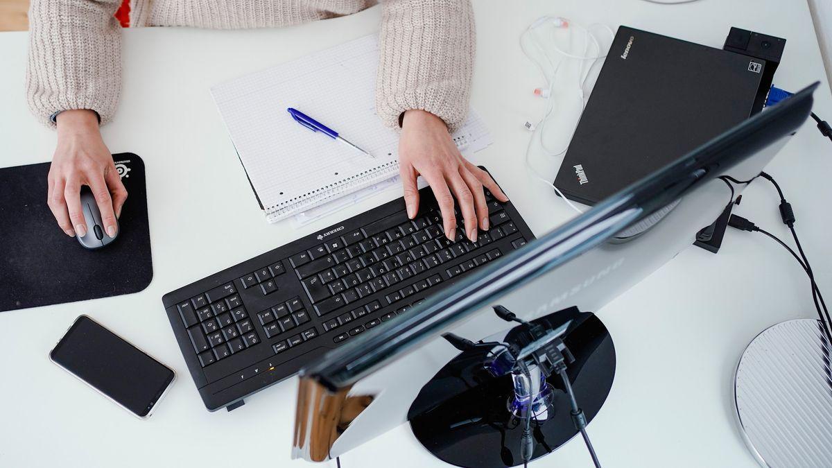 Eine Frau arbeitet an einem Stehtisch (gestellte Szene).