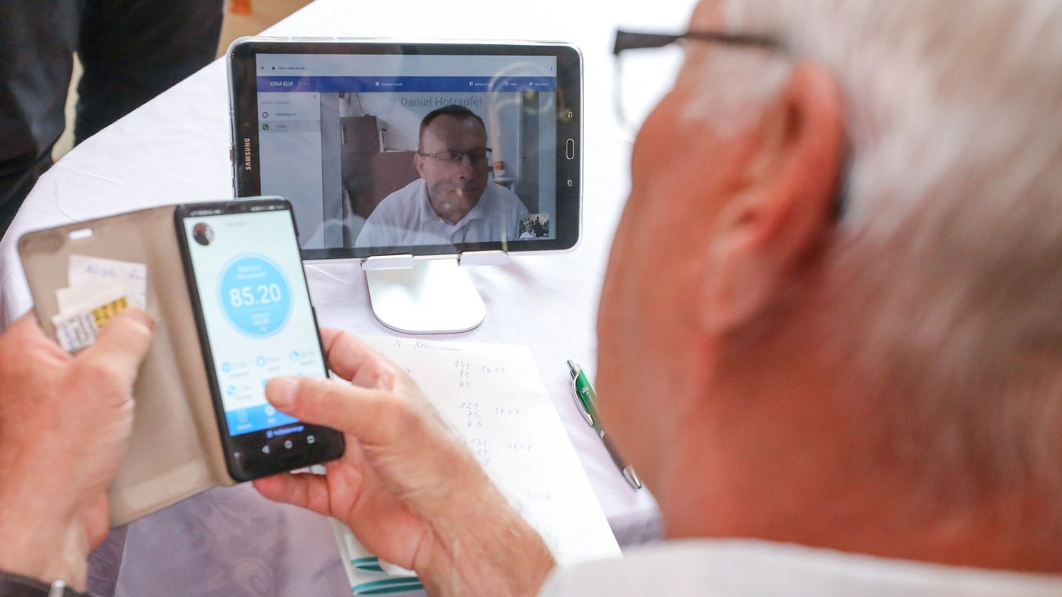 Ein Rentner spricht über einen Videoanruf viaTabletmit seinem Hausarzt.