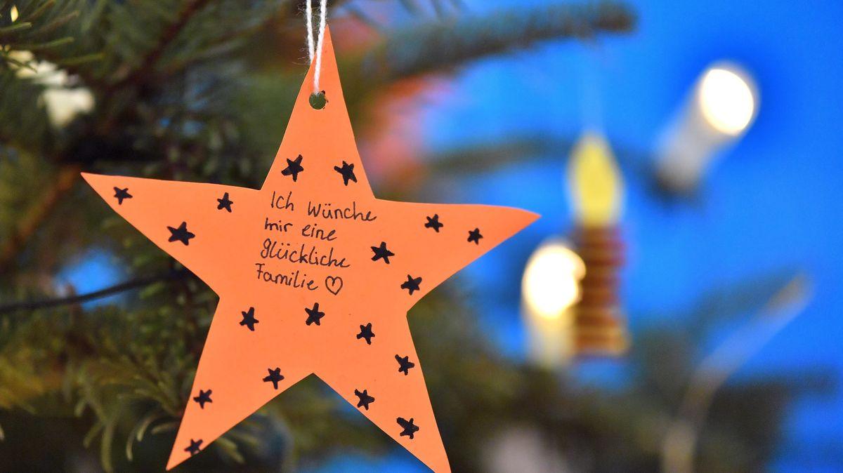"""Weihnachtsbaum mit einem Stern, auf dem jemand die Aufschrift """"Ich wünsche mir eine glückliche Familie"""" angebracht hat."""