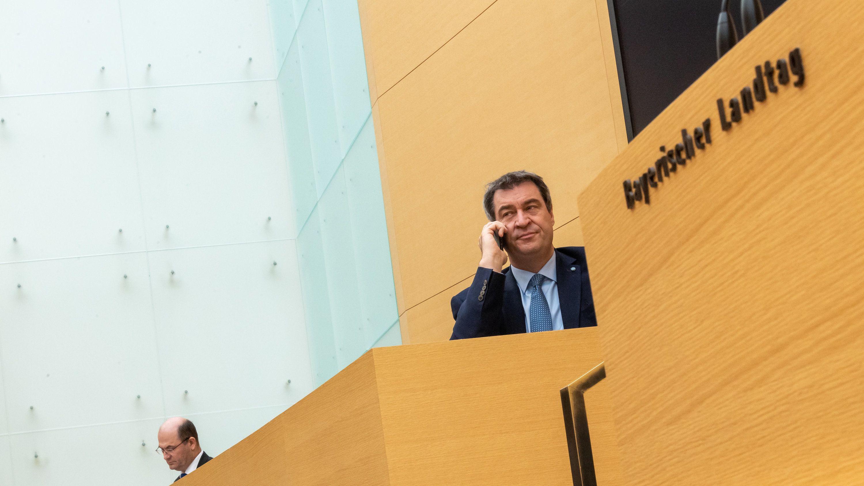 Ministerpräsident Markus Söder telefoniert vor Beginn der Sitzung des bayerischen Landtags neben Albert Füracker (CSU), Staatsminister der Finanzen, Landentwicklung und Heimat.