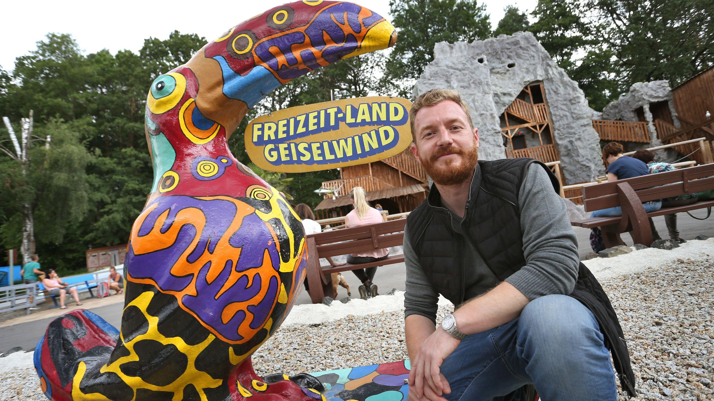 Geiselwind: Parkbetreiber Matthias Mölter hockt im Freizeit-Land Geiselwind mit einem Deko-Vogel vor einem seiner Fahrgeschäfte