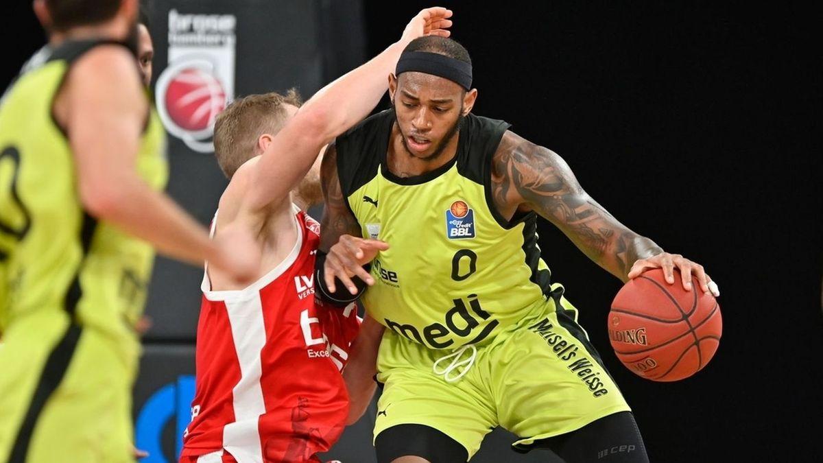 Zwei Basketball-Spieler im gelben und roten Trikot kämpfen um den roten Basketball (Szene aus dem Derby Medi Bayreuth gegen Brose Bamberg im Dezember 2020 in Bamberg)