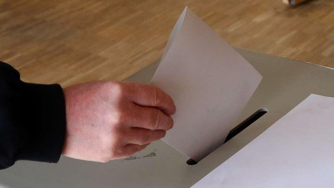 Ein Wähler steckt einen weißen Wahlschein in die Wahlurne (Symbolbild).