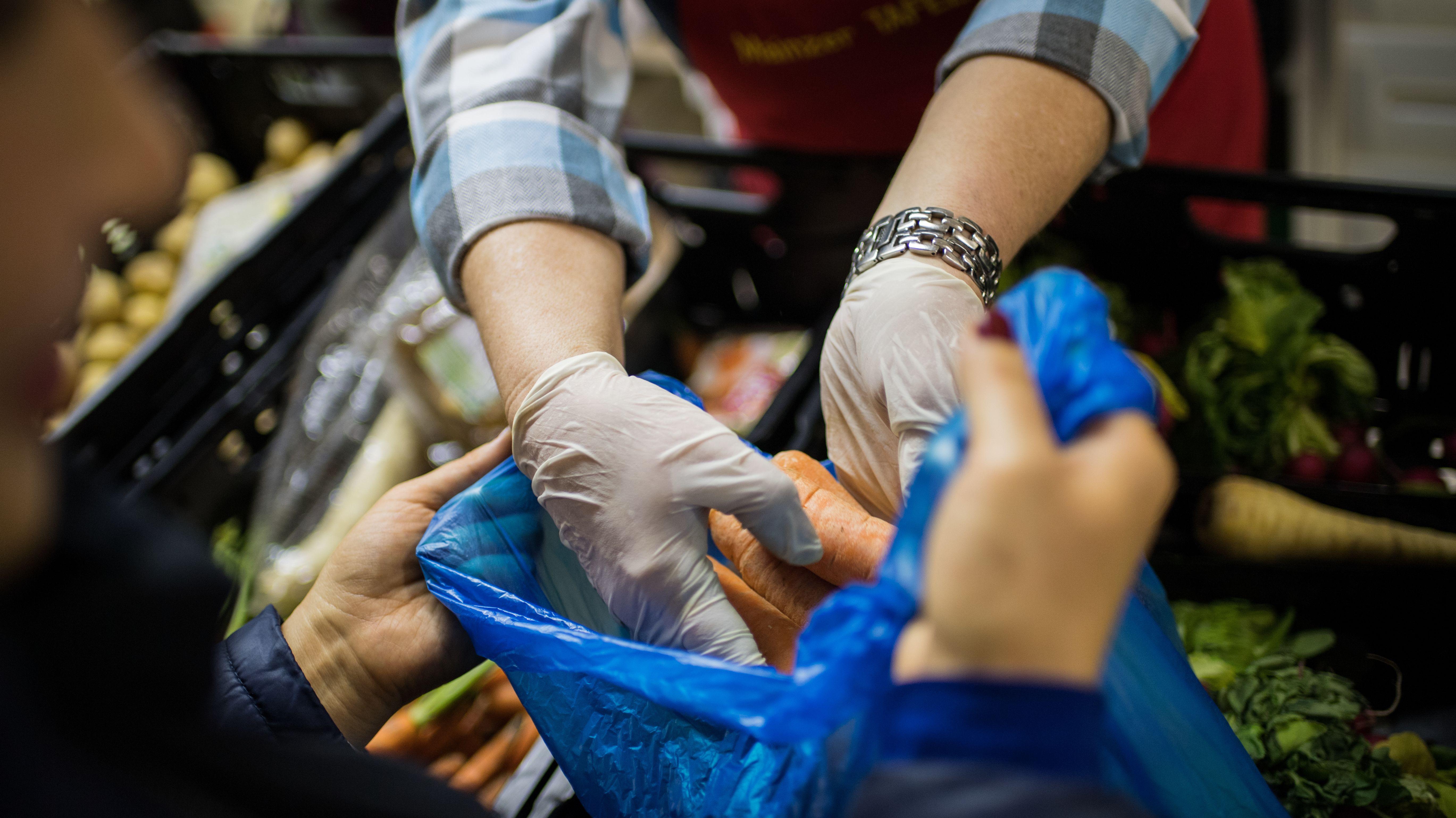 Mitarbeiter einer Tafel packt Lebensmittel in eine Plastiktüte (Symbolfoto).