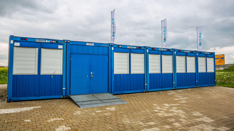 Blaue Container mit Rolladenfenster und Türen stehen bereit, um bald als Übergangs-Lebensmittelladen zu dienen