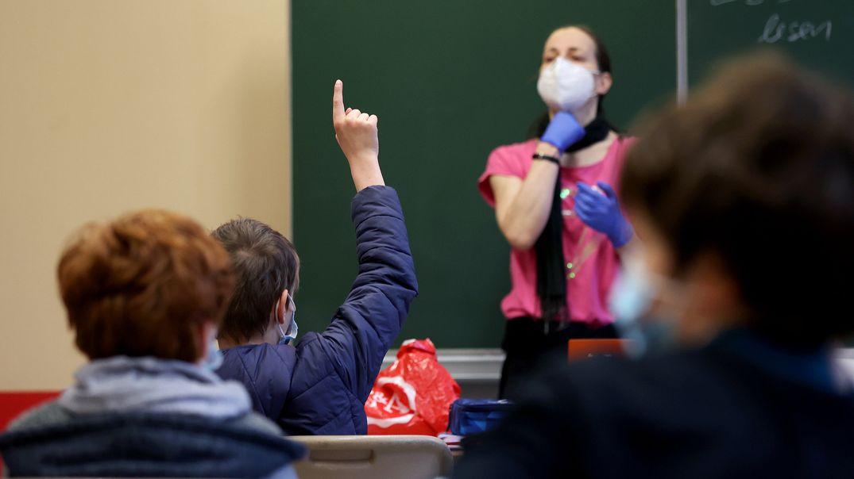 Ein Fünftklässler meldet sich während des Präsenzunterrichts in einem Klassenzimmer.