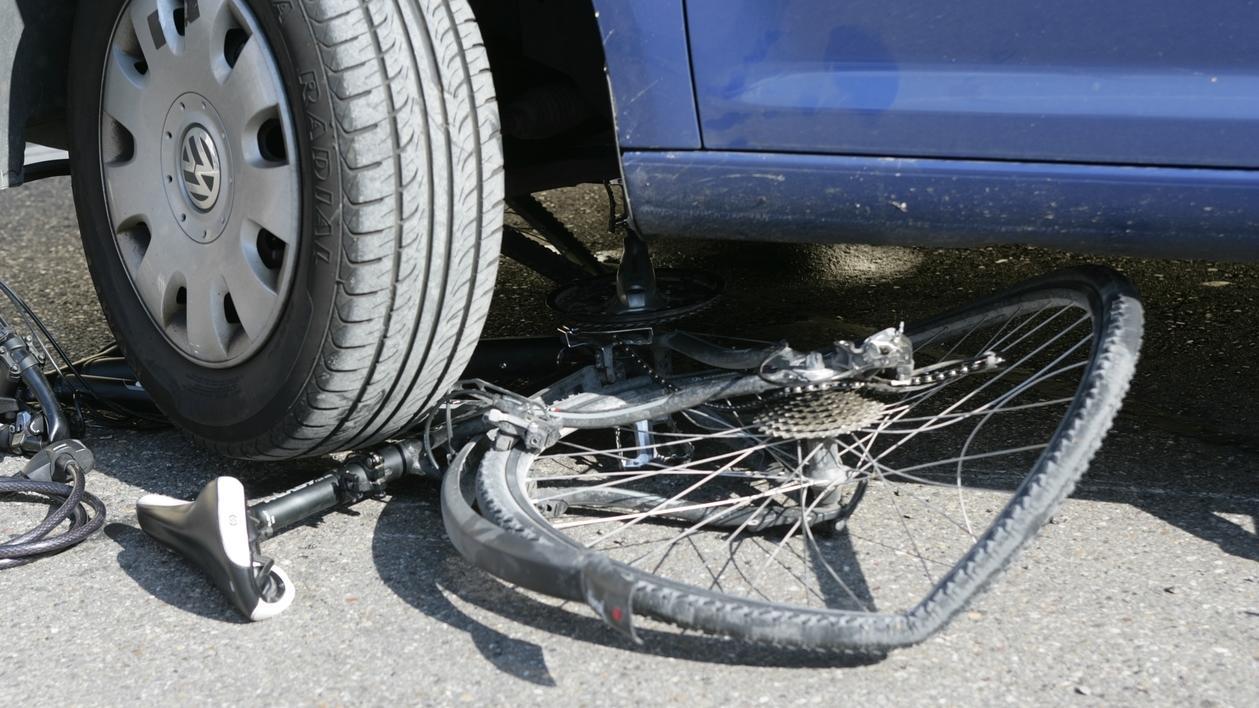 Zerstörtes Fahrrad unter einem Pkw